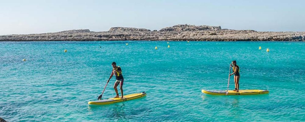 Conoced Menorca remando sobre una tabla de surf